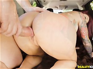 Monique Alexander blows a gigantic wood in the car